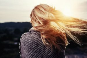 Image of a girl outdoors with her hair shining in the sun
