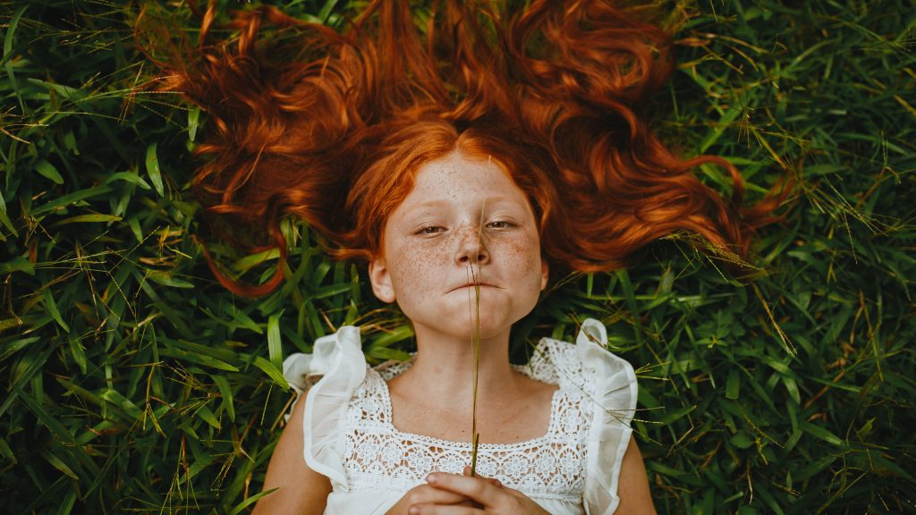 An image of a kid with long red hair lying on grass